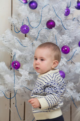Baby boy under Christmas fir tree