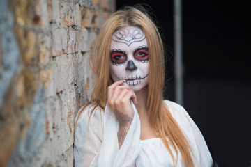 Portrait of a young girl in the image of Santa Muerte