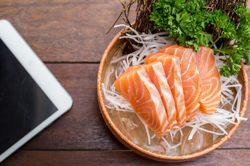 Salmon with a tablet on a wooden table.
