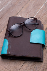 Diary with glasses on a wooden table.