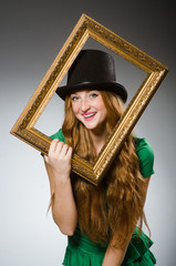 Woman wearing green dress holding picture frame