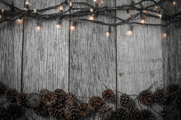 Christmas Lights and Pine cones on Rustic Wood Background