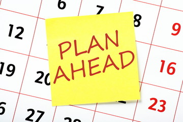 The phrase Plan Ahead written on a yellow sticky note