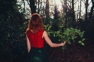 Woman in forest with holly in her hand