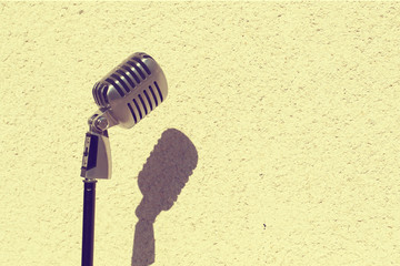 Silver vintage microphone in the studio on wall background