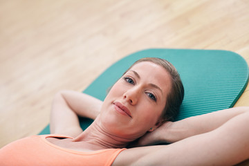 Beautiful woman while lying on gym floor