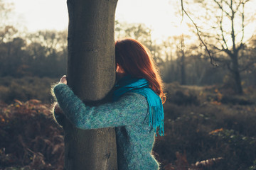 Woman hugging tree at sunset