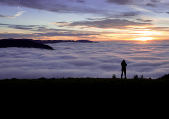 silhouetted photographer standing above fog on hill