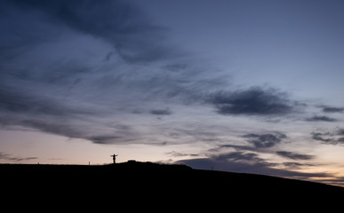 silhouetted hiker standing in sunset sky