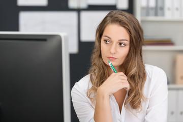 frau im büro schaut nachdenklich zur seite