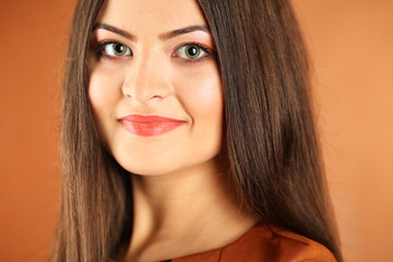 Portrait of a beautiful young woman in a brown background