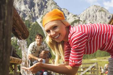 Österreich, Salzburger Land, Frau trinkt Wasser, Mann im Hintergrund