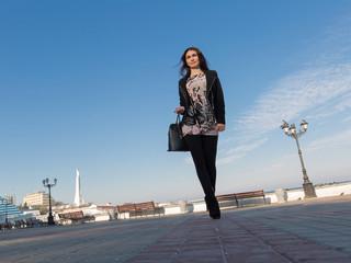 Cute business woman walks outside