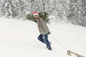 Mann im Schnee, trägt Weihnachtsbaum und zieht Schlitten