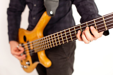 Close up of a brown bass guitar with hands