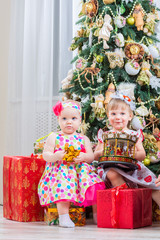 Two baby girls with christmas present