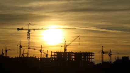 silhouettes of construction cranes at sunset