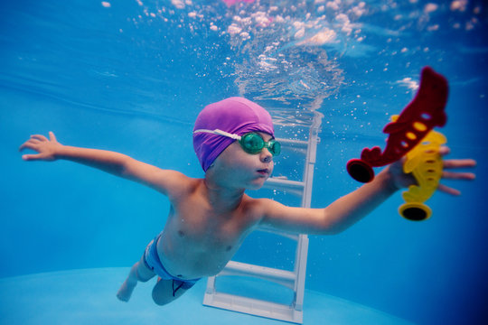 child dives into the pool for a toy