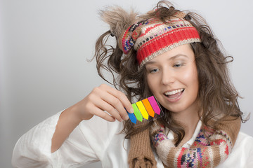 Girl with a knitted hat holding sticky note arrow highlighter ta