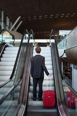 business travel, man with luggage on escalator in airport