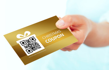 gold christmas coupon holded by hand over white