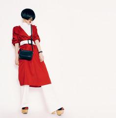Portrait fashionable brunette in a red cloak on a white backgrou