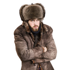 Young bearded man in the coat and earflaps hat, feel cold