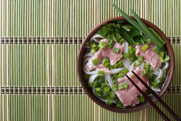 Pho Bo soup with beef rare, rice noodles and fresh herbs