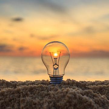 Close up light bulb on sunset beach, energy concept