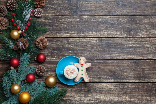Cappuccino with christmas tree shape and gingerbread man on wood