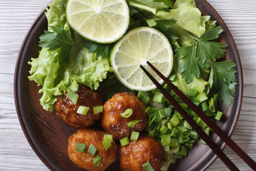 Fish balls with salad and chopsticks close-up. top view