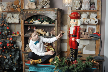 Christmas boy and the Nutcracker around Christmas tree with gift