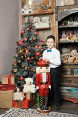 Christmas boy and the Nutcracker around Christmas tree with gift