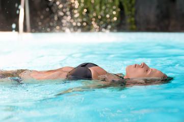 Beautiful sexy woman swims in pool