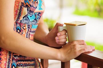 Young woman enjoying a mug of beverage.