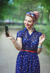 Beautiful woman in fifties style with braces taking picture of h