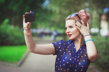 Beautiful young woman in fifties style taking picture of herself