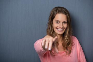 lachende frau zeigt mit dem finger nach vorn