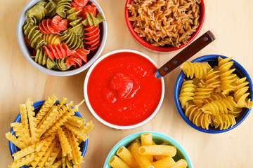Variety of uncooked italian pasta on wooden table