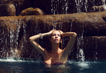 sexy woman in bikini relaxing under waterfall in Thailand