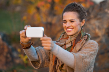Happy young woman in autumn evening outdoors taking photo