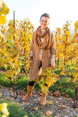 Full length portrait of happy young woman in autumn vineyard