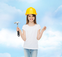 smiling little girl in hardhat with hammer