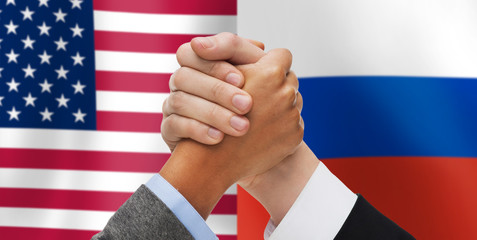 hands armwrestling over american and russian flags