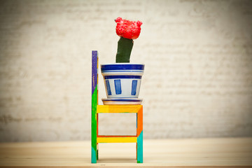 Toy wooden chair and cactus in a pot