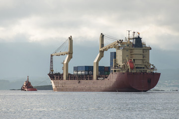 tow boat is towing the tanker from the port