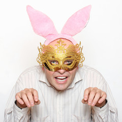 Funny picture of man with paper mask and rabbit ears.