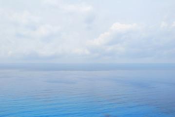 Blue open sea water under cloudy sky