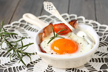 Fried egg with bacon, tomato and rosemary on wooden background