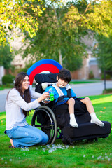 Biracial older sister playing outdoors with disabled little brot